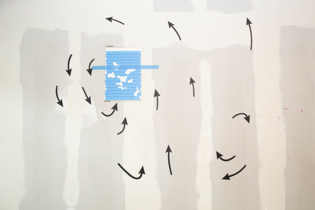 title: H-L black arrows circle around a blue paper with organic shapes cut out. The arrows are made from sticker material and the blue is tape