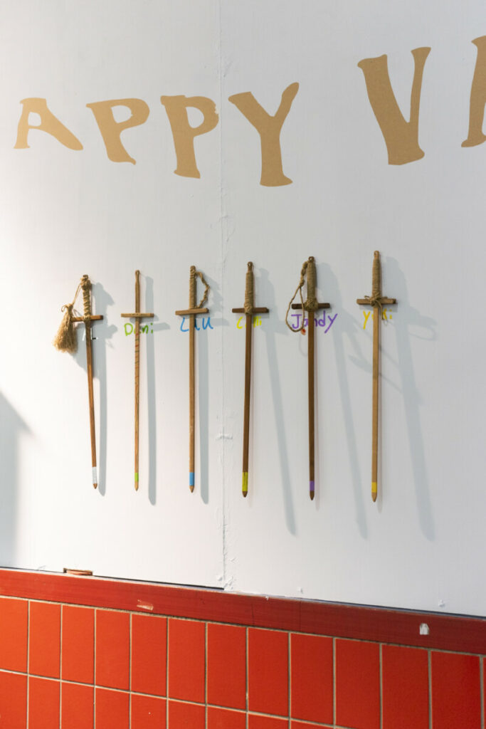 Wooden swords on a light blue wall, happy valley written above. each sword has a sticker underneath with the names of the participants of Hgtomi Rosa