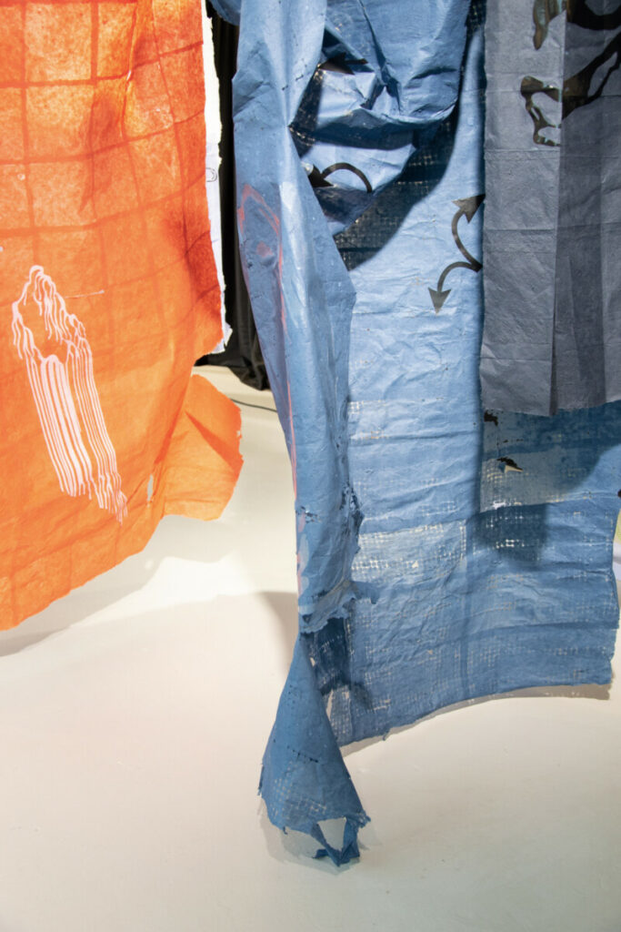 detail of the murmur installation. A blue paper with black arrows and a faded black paper. An orange paper with a light pink sticker in the background. Fashionclash New Fashion Narratives papier