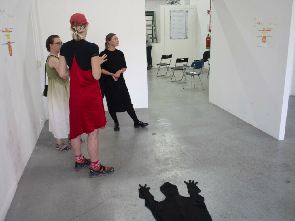 Case study group show at the hgtomi Rosa space. three people are discussing the sunrise works